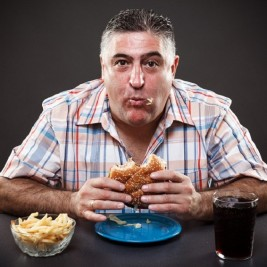 Portrait of a greedy man eating burger on gray background